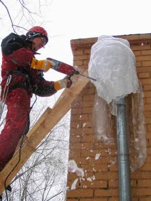 Очистка крыши жилого дома от снега. Удаление нависающих сосулек на водосточной трубе.  Очистка водостока на крыше дома.